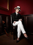 Female mafia-boss. With hat sitting on wooden chair Stock Photography