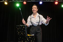 Female magician performing show on stage Stock Image