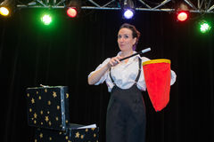 Female magician showing trick with magic wand Stock Image
