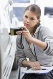 Female maintenance engineer checking car paint with equipment in workshop Stock Photography