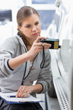 Female maintenance engineer checking car paint with equipment in workshop Royalty Free Stock Photos
