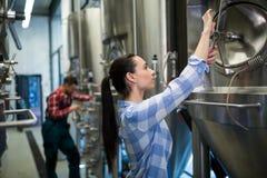 Female maintenance worker examining brewery machine Royalty Free Stock Photography