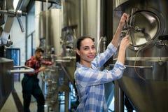 Female maintenance worker examining brewery machine Stock Photo