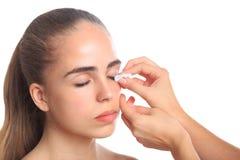 Girl taking off make-up with eyes on white isolated background royalty free stock photo