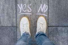 The female makes a choice yes or no. White shoes Stock Images