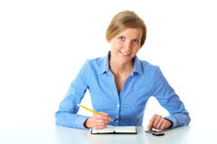 Female makes notes in her diary and check mobile Stock Photo