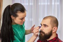 Female makeup artist applying foundation. Royalty Free Stock Photos