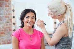 Female makeup artist applying professional brush for eyes of  woman Stock Image