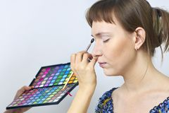 Female makeup model and visagiste hand with eyeshadow brush and pallette - centered Stock Photo