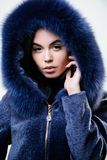 Female with makeup wear dark blue soft fur coat. Woman wear hood with fur. Fashion concept. Girl elegant lady wear royalty free stock photo