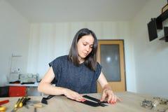Female making belt to order. royalty free stock photos