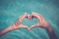 Female making heart shape with hands in water royalty free stock photo