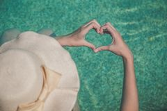 Female making heart shape with her hands in swimming pool stock photos
