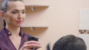 Female making modern hairdo with hair spray and comb, close shot. Stylist in dark red dress, recorded in barbershop. Selective soft focus. Blurred bacground stock footage