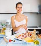 Female making tasty Italian pizza Stock Photography