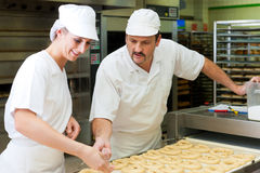 Female and male baker in bakery. Female and male baker baking fresh bread in the bakehouse, they produce brezn Royalty Free Stock Image