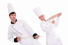 Female and male chefs. Two chefs playing kitchen utensils Stock Photography