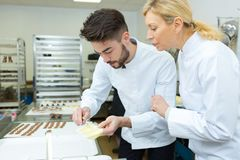 Female and male chocolate maker stock photography