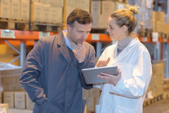 Female and male colleagues checking stocks in warehouse Stock Photos