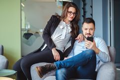 Female and male colleagues looking at mobile phone and smiling. While sitting on the chair together royalty free stock photo
