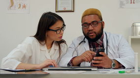 Female and male doctors discussing something looking at the phone stock video footage