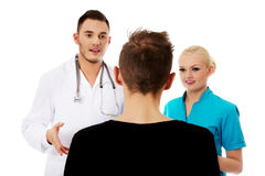Female and male doctors and patient Stock Photos