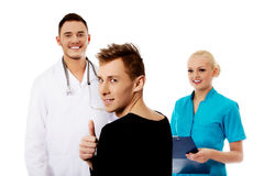 Female and male doctors and patient with thumb up Royalty Free Stock Images