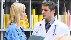 Female and male doctors talking in hospital footage. Young female and male doctors talking in hospital footage in high definition stock footage
