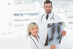 Female and male doctors with xray at medical office Stock Photos