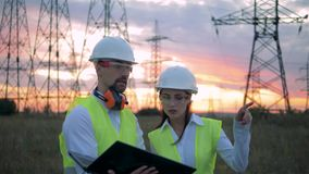 A female and a male engineers are having a discussion in front of ETL. HD stock video footage