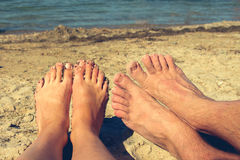 Female and male feet on the background of blue sea. couple lying and resting on the beach. Royalty Free Stock Photos