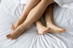 Female and male feet on comfortable bed, closeup top view. Female and male feet on soft comfortable bed mattress, sexy romantic couple relaxing together touching Royalty Free Stock Photography
