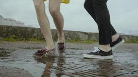 Female and male feet dance in a rainy pool on a sewage grid in summer. Closeup of female and male feet dancing optimistically in a rainy pool on a sewage grid stock footage