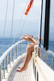 Female and male feet on a lounger on the ship. Summer vacation. On yacht Royalty Free Stock Photos