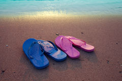 Female and male flip flop sandals on the beach. Romantic beach scene. Female and male flip flop sandals on the beach at sunrise Stock Photography