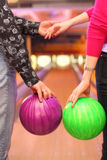 Female and male hands with balls in bowling club Royalty Free Stock Images