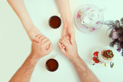 Female and male hands with cups of tea. Close-up Stock Image