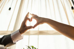 Female and male hands forming a heart shape with sunlight at restaurant interior. Concept of love, wedding. Stock Photos