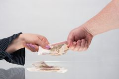Female and male hands hold banknotes. Well-groomed female hand with manicure and male hold banknotes Russian rubles Royalty Free Stock Photo