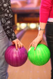 Female and male hands holding balls in bowling c Royalty Free Stock Image