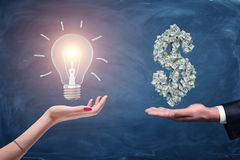 A female and a male hands holding a large bright light bulb and a dollar sign made of many money bills. Money and wealth. Profitable ideas. Financial streak royalty free stock images