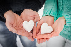 Female and male hands with snow hearts Stock Images