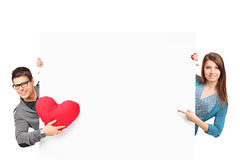 Female and male with heart shaped object. Smiling female and male with heart shaped object posing behind a white panel isolated on white background Royalty Free Stock Images