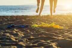 Female and male legs with bikini and swimming trunks on the sand on a sunset background. Concept Royalty Free Stock Images