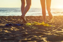 Female and male legs with bikini and swimming trunks on the sand on a sunset background. Concept Royalty Free Stock Photography