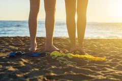 Female and male legs with bikini and swimming trunks on the sand on a sunset background. Concept Stock Image