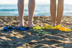 Female and male legs with bikini and swimming trunks on the sand on a sunset background. Concept Stock Photography