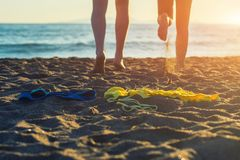 Female and male legs with bikini and swimming trunks on the sand on a sunset background. Concept Stock Photo
