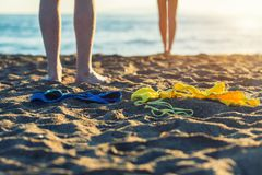 Female and male legs with bikini and swimming trunks on the sand on a sunset background. Concept Stock Images