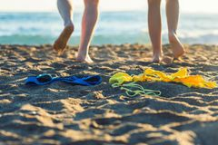 Female and male legs with bikini and swimming trunks on the sand on a sunset background. Concept Royalty Free Stock Photos